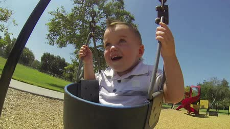 POV Cute baby boy in swing at park on summer day  Wideo