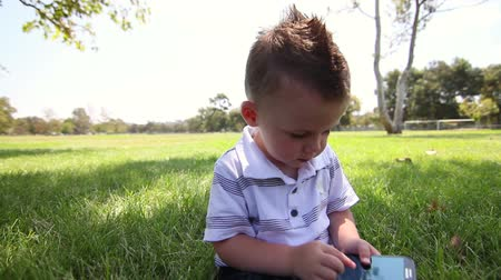 közepes : Young cute baby boy using phone touch screen at park.