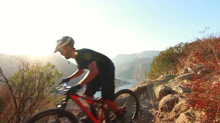 pohoří : Slow Motion Extreme Mountain Biker Riding Down Hill At Sunset