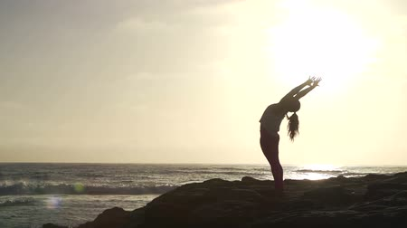 obtížný : Slow Motion Woman Practicing Yoga Stretching Pose At Sunset Dostupné videozáznamy