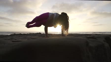 Woman Practicing Difficult Advanced Yoga Pose At Sunset With Lens Flare