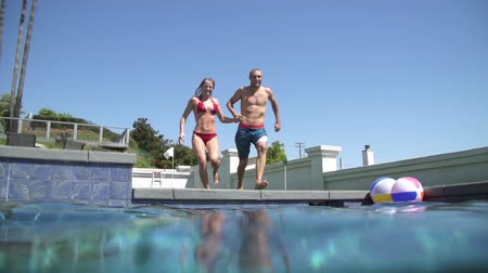 jump : Young Happy Couple Holding Hands Running And Jumping Into Pool Stock Footage