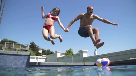медовый месяц : Young Happy Couple Holding Hands Running And Jumping Into Pool Стоковые видеозаписи