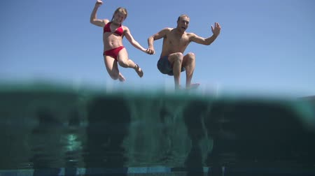Young Happy Couple Holding Hands Running And Jumping Into Pool Wideo