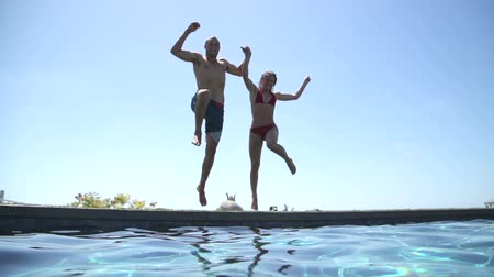 uszoda : Happy Couple Holding Hands And Jumping Into Swimming Pool Stock mozgókép