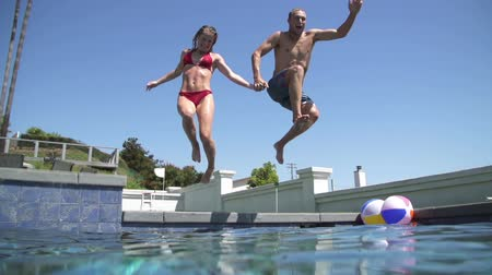 fitnes : Slow Motion Couple Jumping Into Swimming Pool Holding Hands