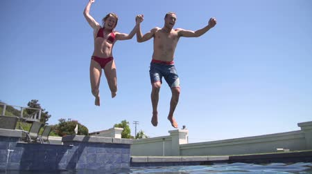 party summer : Couple de mouvement lent de sauter dans piscine tenir par la main