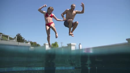 basen : Young Happy Couple Holding Hands Running And Jumping Into Swimming Pool Wideo