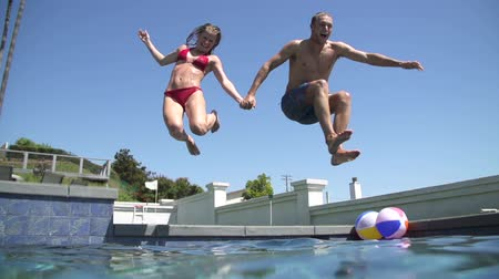 Young Happy Couple Holding Hands Running And Jumping Into Swimming Pool Wideo