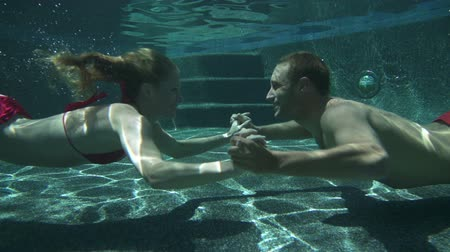 Couple Kissing Underwater In Swimming Pool In Slow Motion