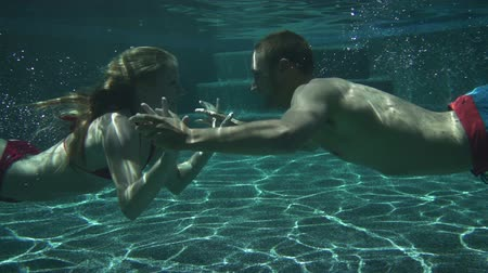 swimming underwater : Couple Kissing Underwater In Swimming Pool In Slow Motion