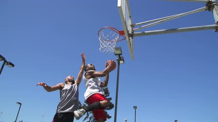 jogadores : Two Basketball Players Playing One on One Outside and Scoring