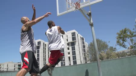 Two Basketball Players Playing One on One Outside and Scoring
