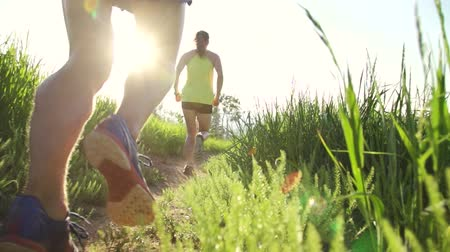 executar : Slow Motion Couple Running Through Grass At Sunset Lens Flare