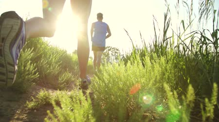Slow Motion Couple Running Through Grass At Sunset Lens Flare