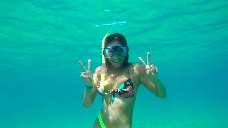 Young Happy Woman Snorkeling Underwater With Peace Sign