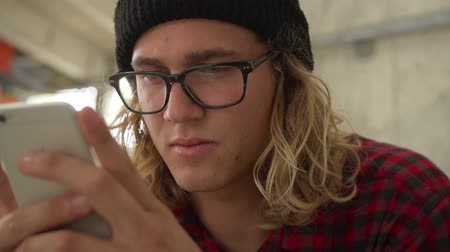Focused Hipster Male Student Looking At Phone