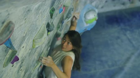 bouldering : Young Woman Rock Climbing Reaching For Hand Hold Stock Footage