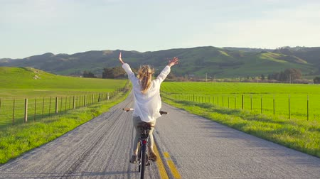 faire velo : Fille Riding Bike Down Country Route Avec Hands Up In Air At Sunset Vidéos Libres De Droits