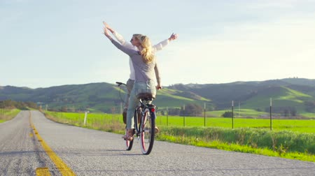 Two Girls Riding Bike At Sunset With Hands Up In Air