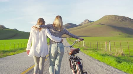 Two Girl Best Friends Walking Down Country Road With Bike At Sunset