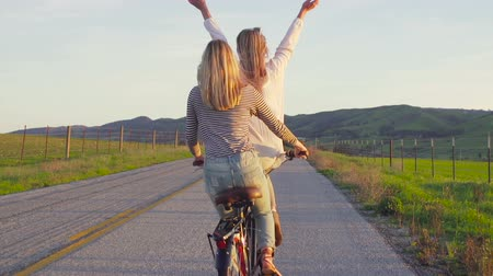 faire velo : Two Girls Riding Bike au coucher du soleil avec les mains en l'air