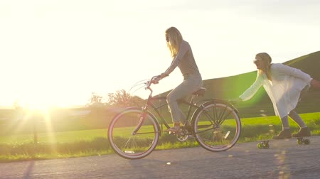 ciclismo : Two Girls Riding Bike And Skateboard Down Hill At Sunset