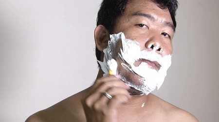 shaving foam : Men shaving in the bathroom.