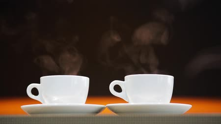 xícara de café : two hot cups of coffee standing on the table