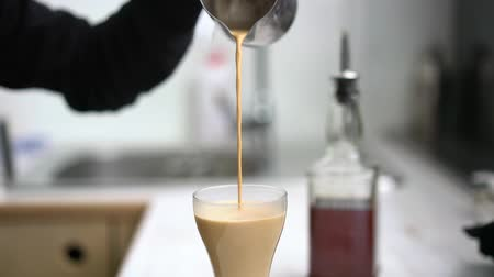 латте : Barista pours coffee with milk into a glass Стоковые видеозаписи