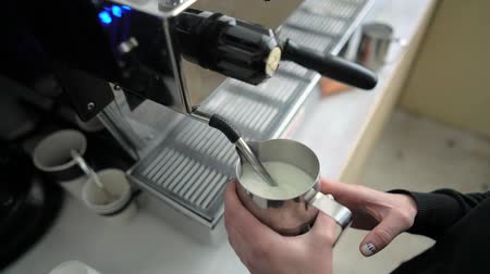 caffe : Barista steaming milk in a stainless steel tumbler