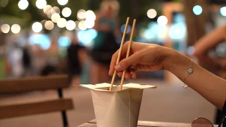 Cardboard box of asian food and hand holding chopsticks. Stock Footage