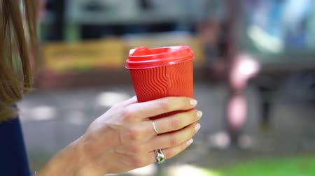 Woman outdoors holds a red plastic cup in her hand.