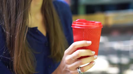 plastic cups : Woman outdoors holds a red plastic cup in her hand.