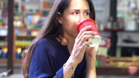 Woman talking on mobile cell phone and drinking from a red plastic cup Stock Footage