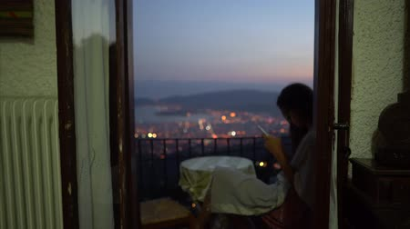 Woman sitting on balcony and using smartphone at home in evening