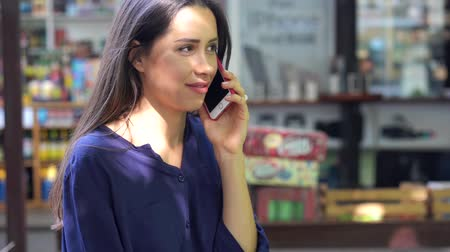 Young brunette girl talking on mobile cell phone in a street cafe Stock Footage
