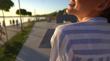 Beautiful young girl posing on camera on the street, sunset Stock Footage