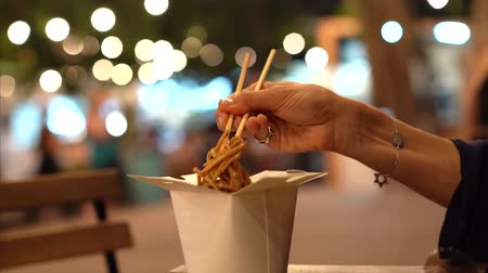 View of woman hand eating noodles with chopsticks