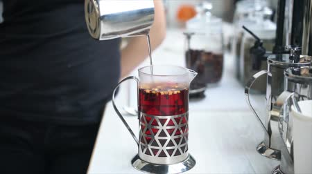 Barista making tea in French press, close view