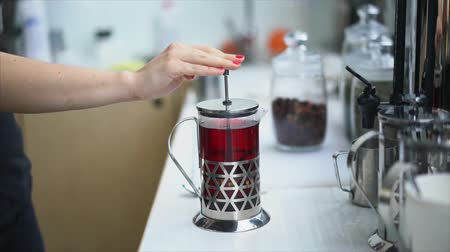 Hand lowers piston of teapot with tea
