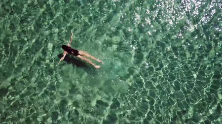 топ : Girl in a black swimsuit swims in the sea. Стоковые видеозаписи