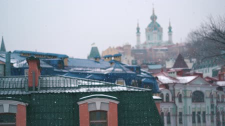 copious snowfall over the city with the roofs of the building and windows Stock Footage