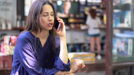 awesome : Young brunette girl talking on mobile cell phone in a street cafe Stock Footage