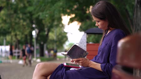 Young woman dressed casually works on a bench in the park. Stock Footage