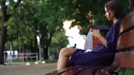 Woman sits on the bench and using smartphone over background the park. Stock Footage