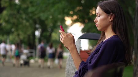 parky : Woman sits on the bench and using smartphone over background the park. Dostupné videozáznamy