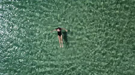 pływanie : Girl in a black swimsuit swims in the sea. Wideo