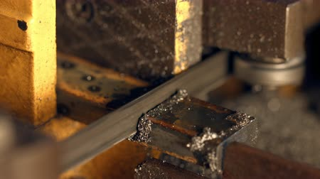 being cut up : Close up of metal bar being cut by swivel metal cutting band saw.