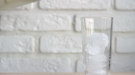 джин : lemonade poured in a glass Cup with ice brick on white background